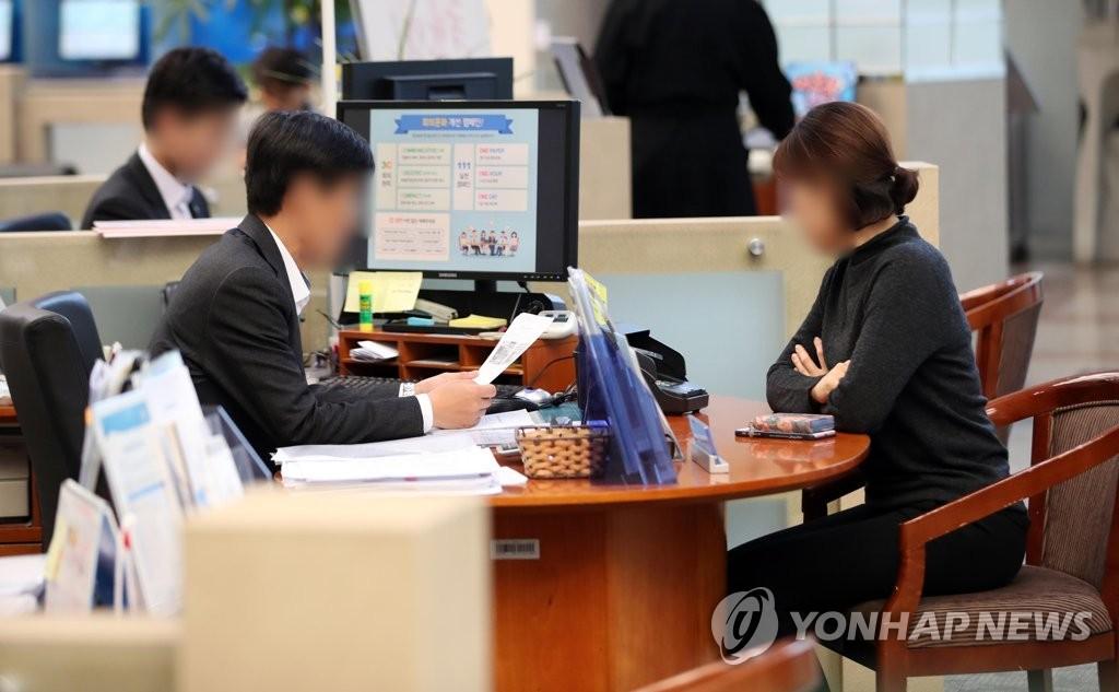 资料图片:2018年11月21日下午,在首尔一家银行,一位顾客在窗口介绍贷款咨询。(韩联社)