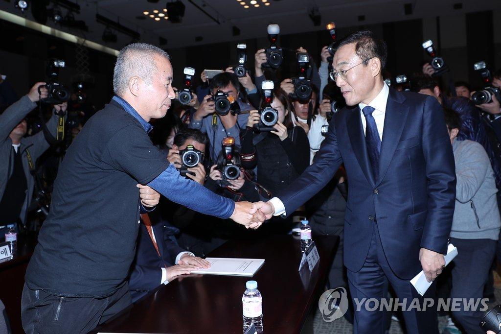 11月23日上午,在仲裁案落实协议签字仪式上,金奇南(右)与半导体厂工人组织代表握手。(韩联社)