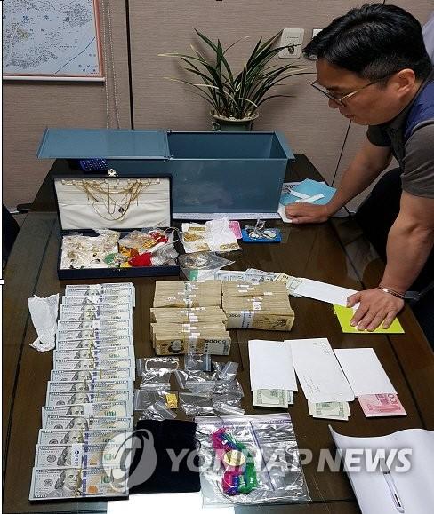 资料图片:图为一名欠税者金库中的现金、美元和贵金属。(韩联社/国税厅供图)