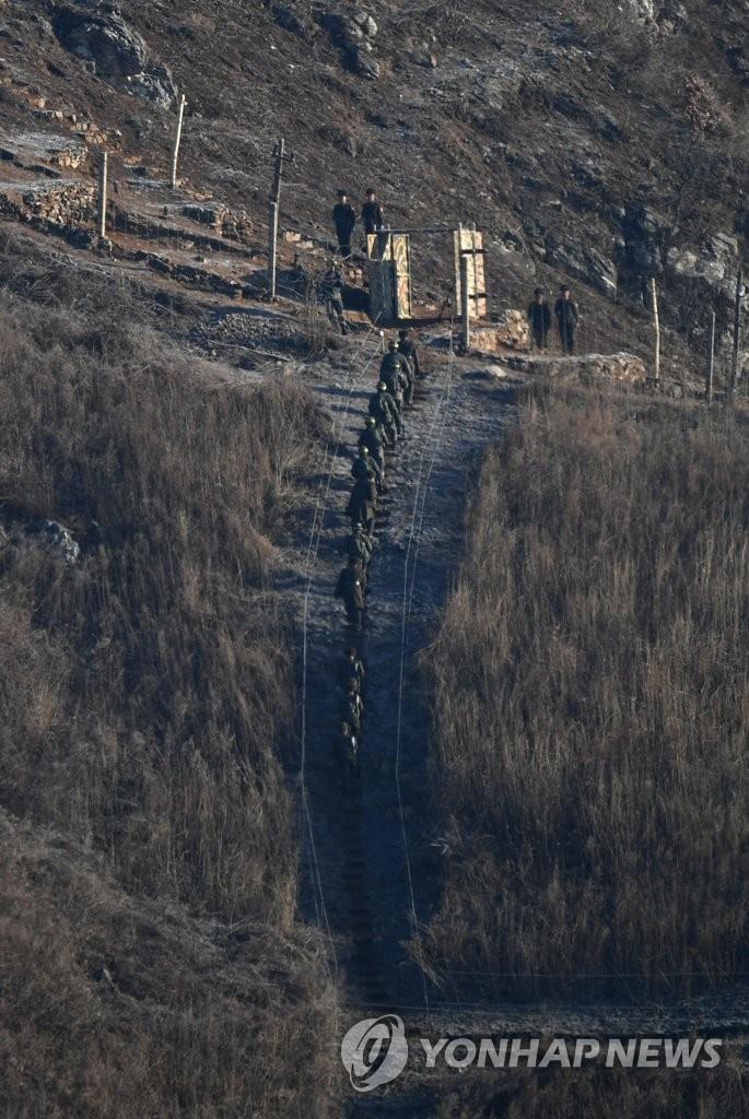 12月12日,在非军事区朝方一侧,韩方人员前往朝方监测哨所检查哨所拆除情况。(韩联社/联合采访团)
