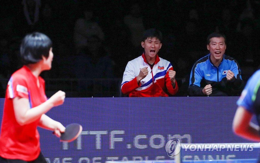 资料图片:12月15日,在仁川南洞体育馆举行的国际乒联世界巡回赛总决赛,韩朝乒乓联队教练组欢呼庆祝韩朝联队得分。(韩联社)