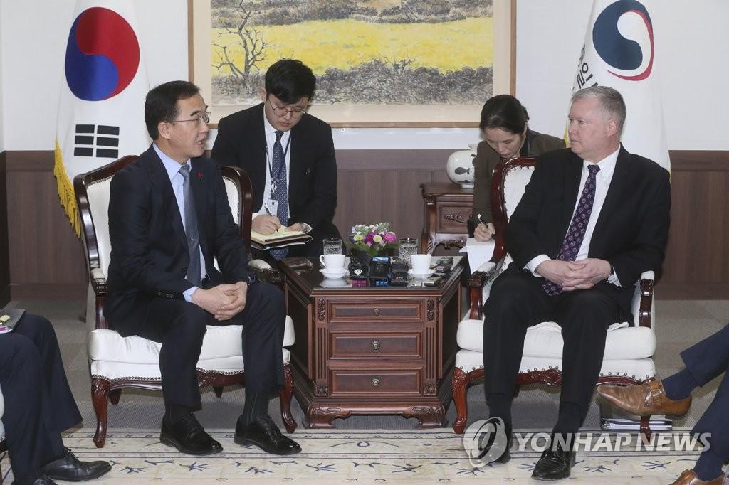 12月21日,在首尔,赵明均(左)与来访的比根交谈。(韩联社)