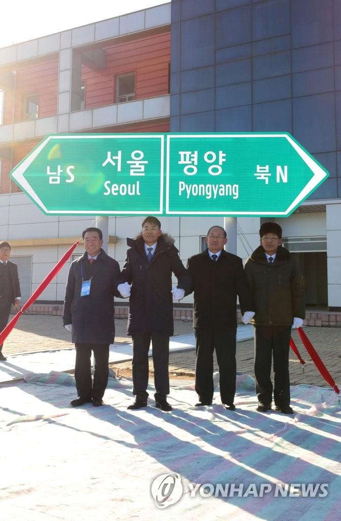 12月26日上午,在开城市板门站,出席韩朝东西海岸铁路公路对接及升级改造项目开工仪式的韩国道路公社社长李康来(左起)、统一部副部长千海成、朝方国土环境保护省副相等人在跨境公路指示牌前合影。路牌示意首尔向南,平壤向北。(韩联社)