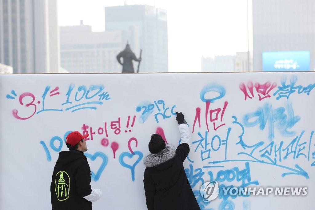 资料图片:2018年12月31日,预告三一运动和大韩国民国临时政府成立将迎百周年的大型留言板设置于首尔光化门广场,两名市民在留言。(韩联社)