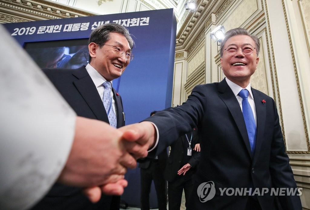 1月10日上午,在青瓦台举行新年记者会后,文在寅(右)与记者握手致意。(韩联社)