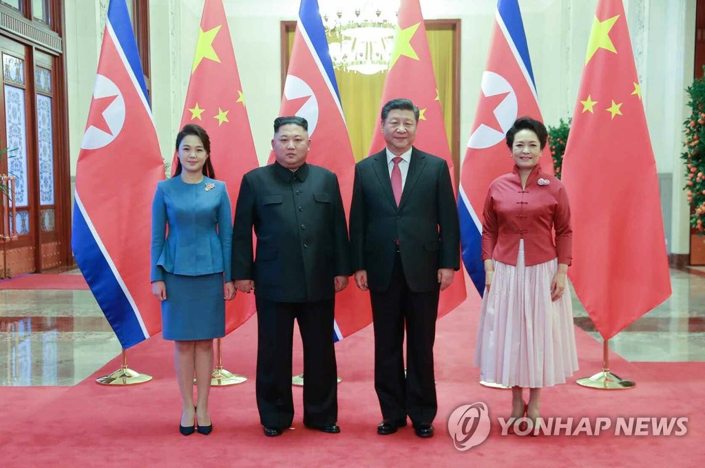 资料图片:朝鲜党报《劳动新闻》1月10日刊登朝鲜国务委员会委员长金正恩第四次访华的消息和照片。图为金正恩(左二)和夫人李雪主(左一)、中国国家主席习近平(右二)和夫人彭丽媛(右一)在北京人民大会堂合影留念。图片仅限韩国国内使用,严禁转载复制。(韩联社/劳动新闻)