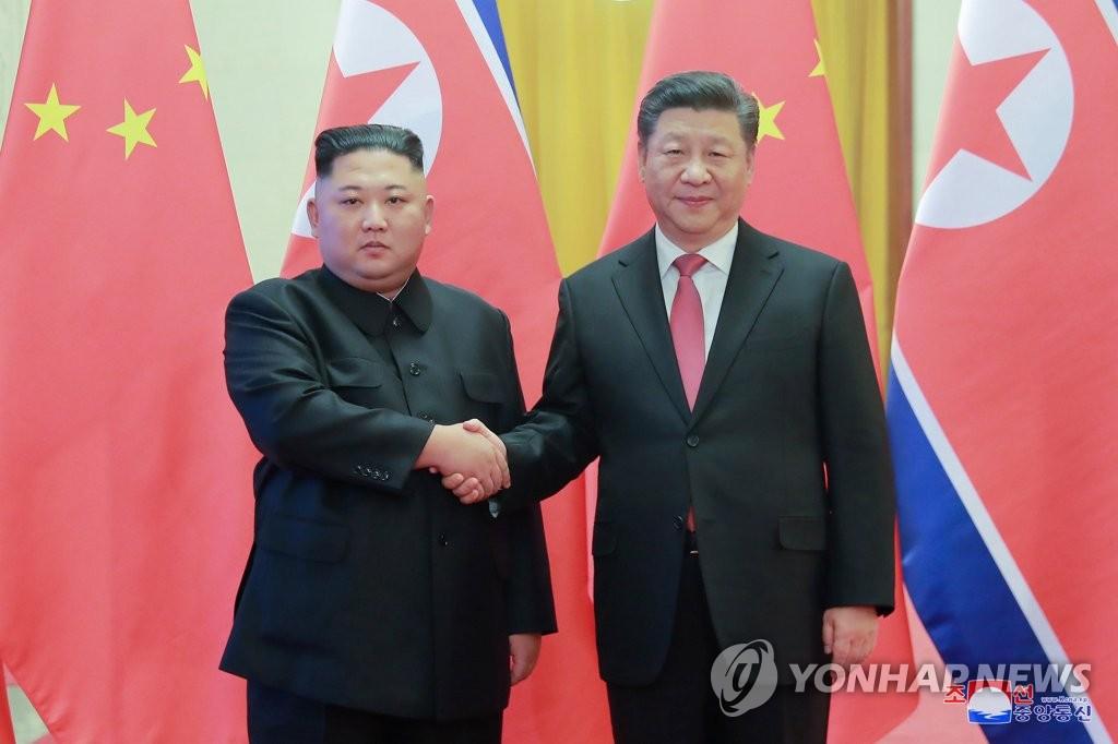 资料图片:金正恩(左)和习近平握手。图片仅限韩国国内使用,严禁转载复制。(韩联社/朝中社)