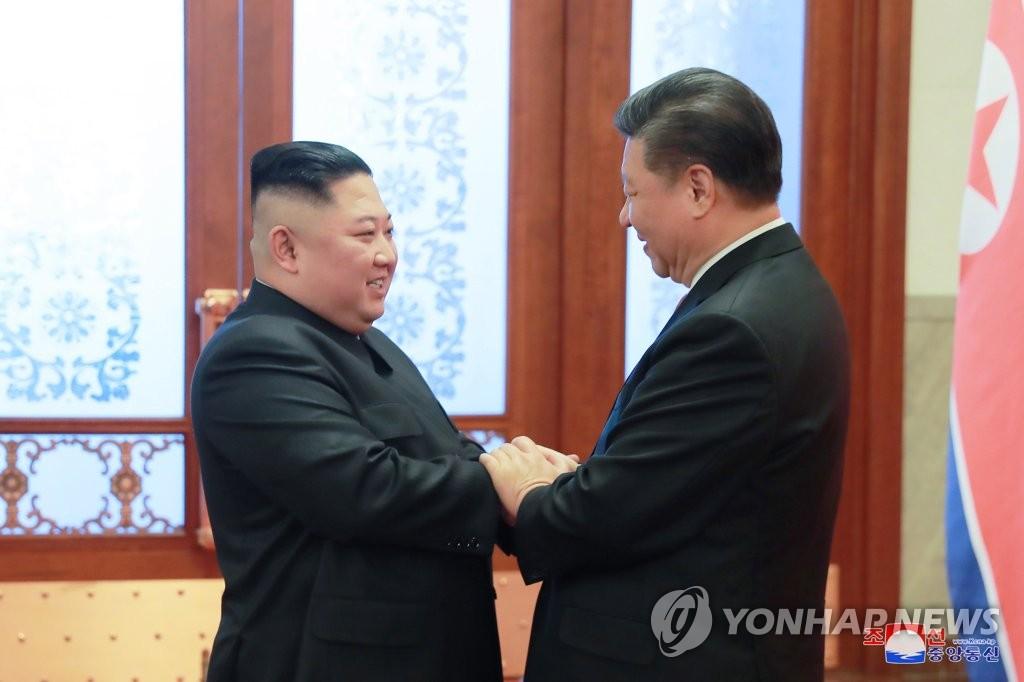 �Y料�D片:金正恩(左)和�近平�H切握手。 �n�社/朝中社(�D片�H限�n�����仁褂茫��澜��D�d�椭疲�