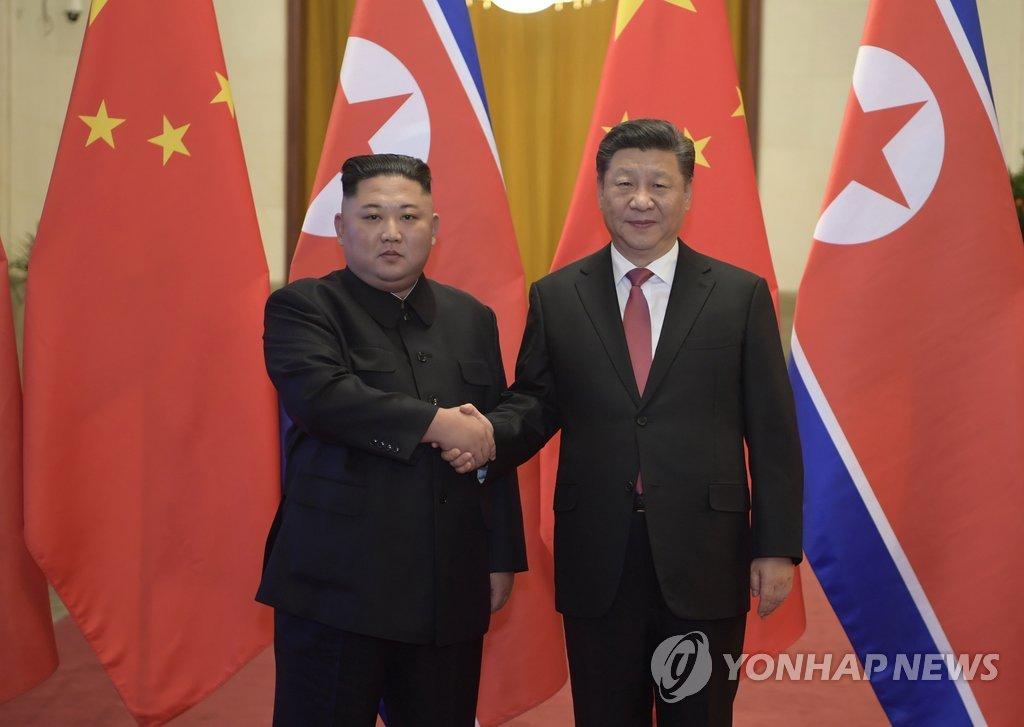 1月8日,在北京人民大会堂,金正恩(左)和习近平在举行会谈前握手。(韩联社/新华社、美联社)