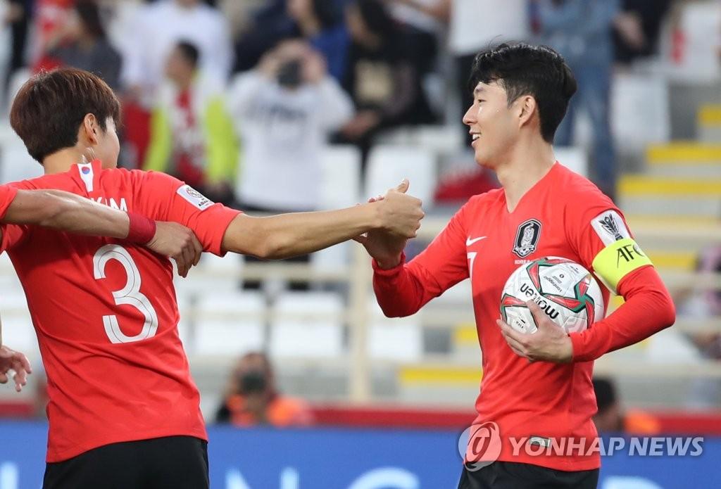孙兴慜(右)创造点球后与队友庆祝。(韩联社)