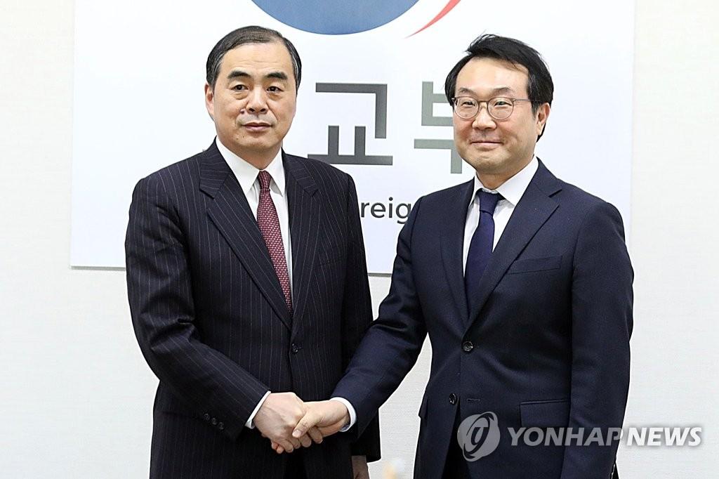 1月17日下午,在首尔,韩国外交部韩半岛和平交涉本部长李度勋(右)与中国外交部副部长兼朝鲜半岛事务特别代表孔铉佑在举行朝核六方会谈韩中团长会议前握手。(韩联社)