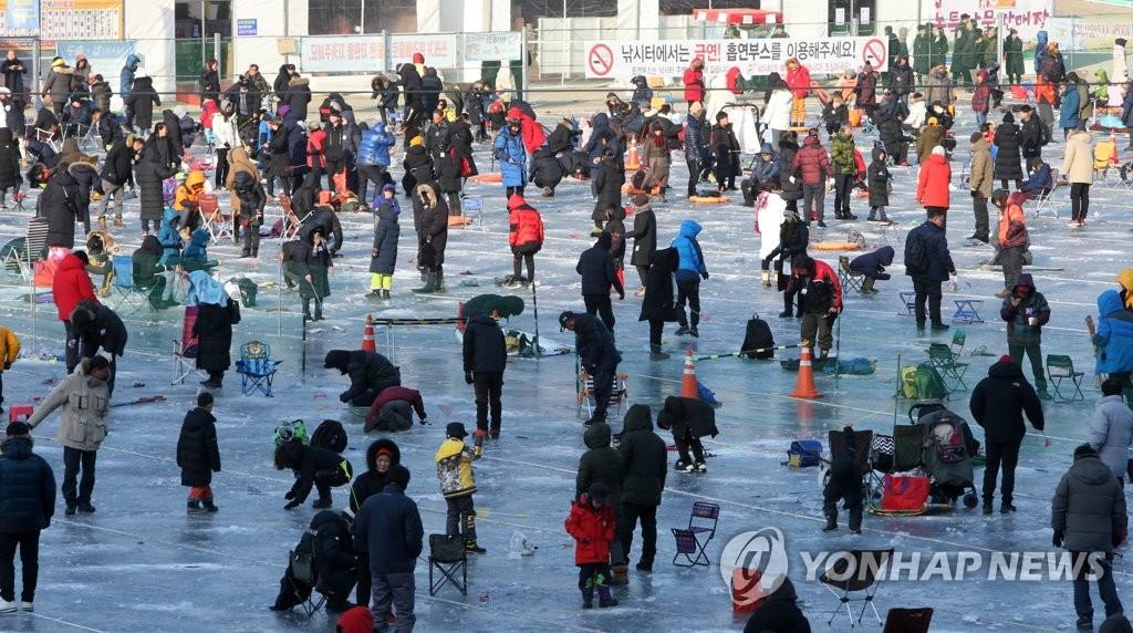 资料图片:1月20日,华川山鳟鱼冰钓场人头攒动。(韩联社)
