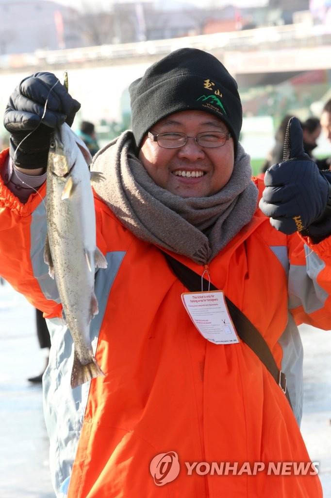 资料图片:1月20日,在江原道华川,参加山鳟鱼庆典的一名游客手举山鳟鱼拍照留念。(韩联社)