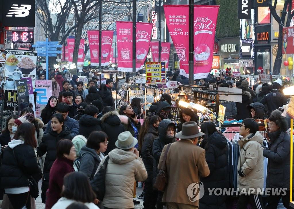 资料图片:2019年韩国购物季期间,首尔商业区明洞挂出购物季条幅。 韩联社