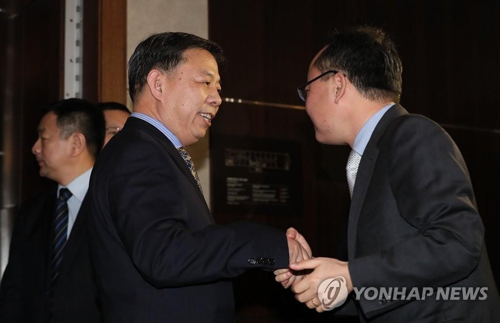 资料图片:1月22日下午,在首尔乐天酒店,韩国环境部气候变化政策官黄晳泰(右)与中国生态环境部国际合作司司长郭敬握手致意。(韩联社)