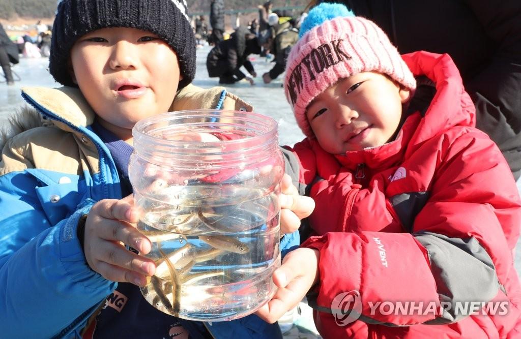 1月26日,在江原道麟蹄郡举行的第19届麟蹄钓冰鱼节上,孩子们展示自己钓上来的冰鱼。(韩联社)