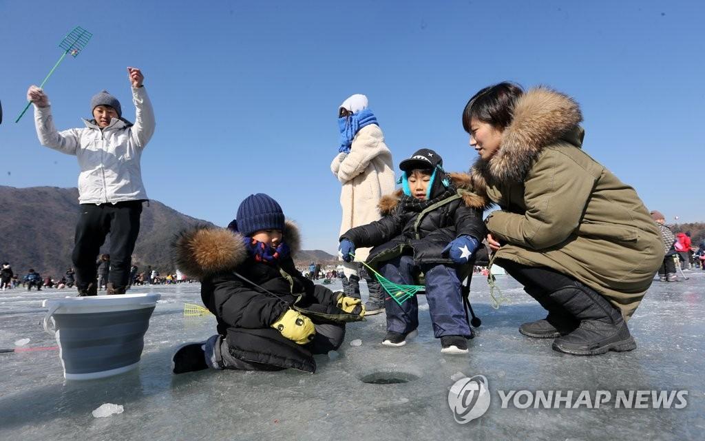 1月27日,在江原道麟蹄郡举行的第19届麟蹄钓冰鱼节上,一家人正在钓冰鱼,度过愉快的时光。(韩联社)