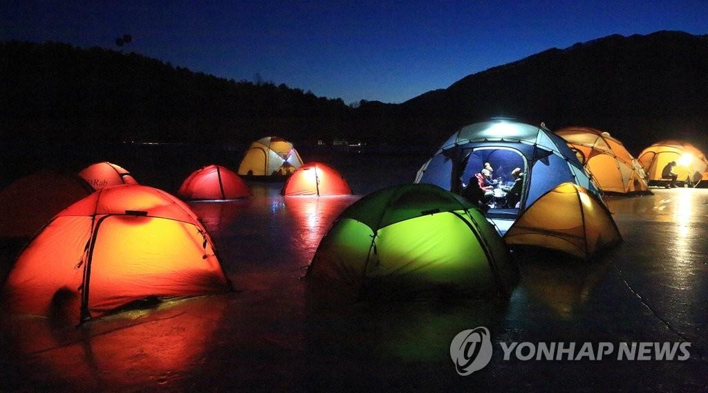 1月28日,在江原道麟蹄郡昭阳江上游冰面上,五颜六色的帐篷点缀着夜幕。(麟蹄郡政府供图)