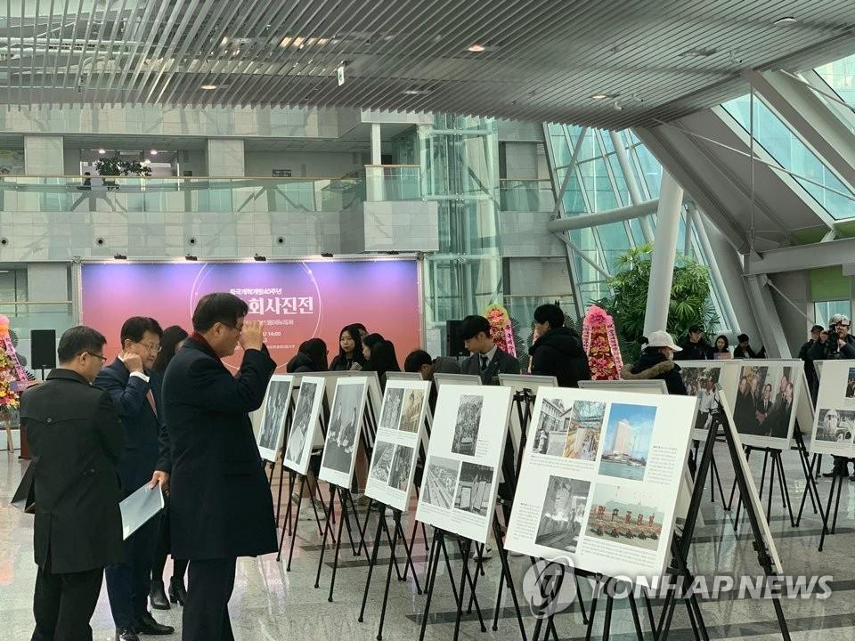 1月31日,中国改革开放40年主题国际巡展在韩国国会议员会馆开幕。图为访客认真观展。(韩联社)