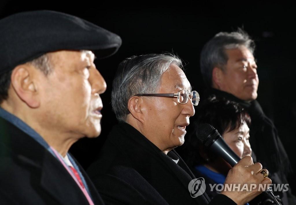 2月12日上午,在首尔市景福宫停车场,金喜中(左二)在赴朝前的记者会上发言。(韩联社)