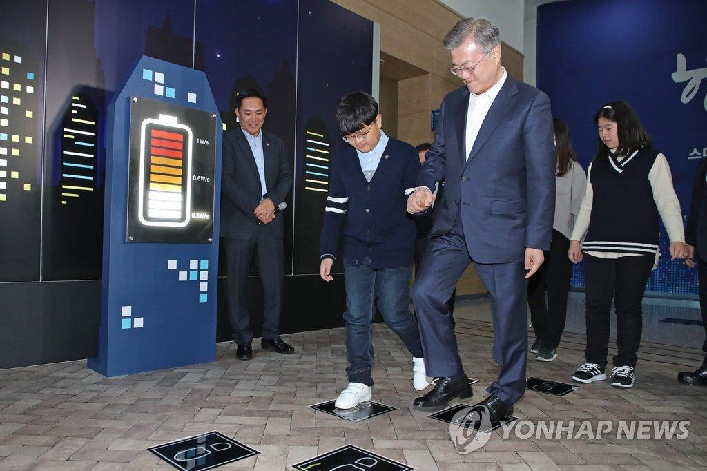 2月13日上午,智慧城市战略发布会在釜山会展中心(BEXCO)举行。图为韩国总统文在寅体验由人体动能发电的智能设备。(韩联社)