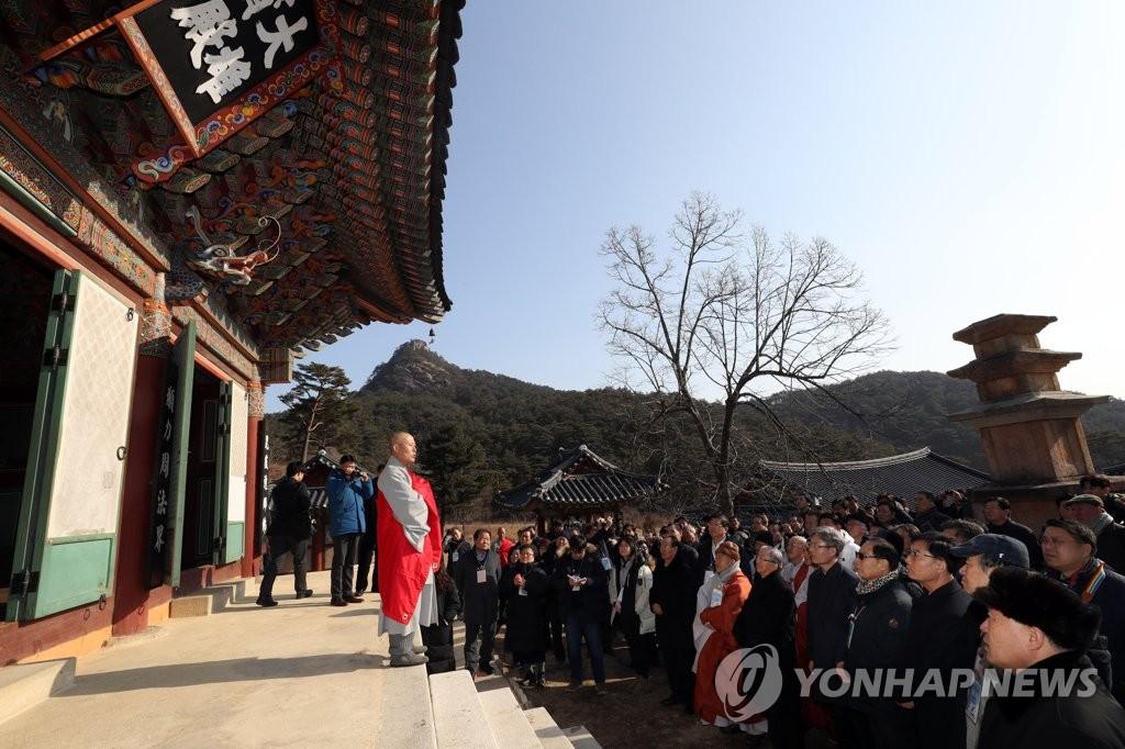 2月13日,在朝鲜金刚山四大名刹之一的神溪寺,出席迎新联谊会的韩朝各界代表一同参观寺院。(韩联社)