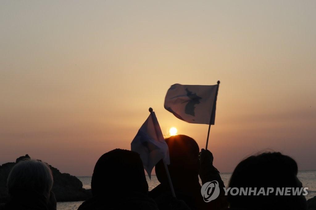 2月13日,在朝鲜海金刚日出景点,出席迎新联谊会的韩朝各界代表挥舞半岛旗一同迎接日出。(韩联社)
