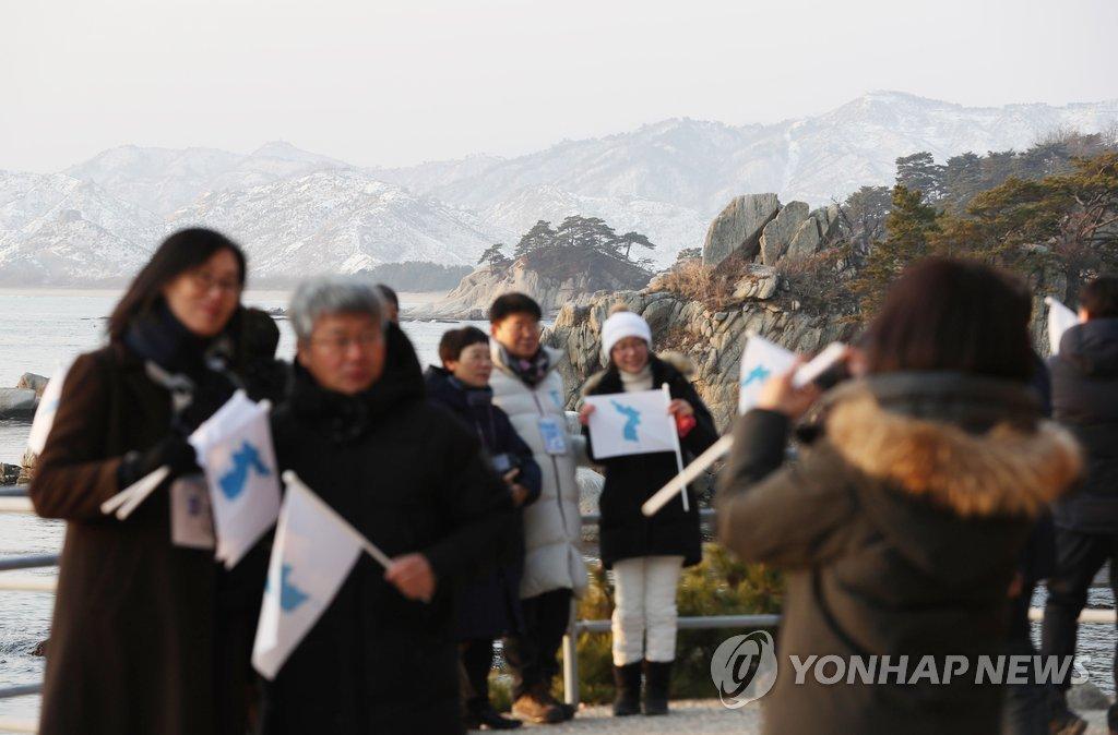 2月13日,在朝鲜海金刚,参加新春联谊会的韩朝人士看日出并合影留念。(韩联社)