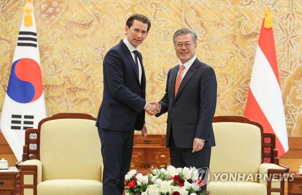 2月14日下午,在青瓦台,韩国总统文在寅(右)与奥地利总理塞巴斯蒂安·库尔茨举行会谈前握手合影。(韩联社)