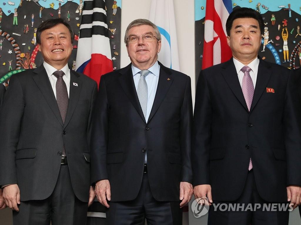 当地时间2月15日,在瑞士洛桑,韩国文化体育观光部长官都钟焕(左)、朝鲜体育相金一国(右)和国际奥委会主席巴赫举行会晤前合影留念。(韩联社)