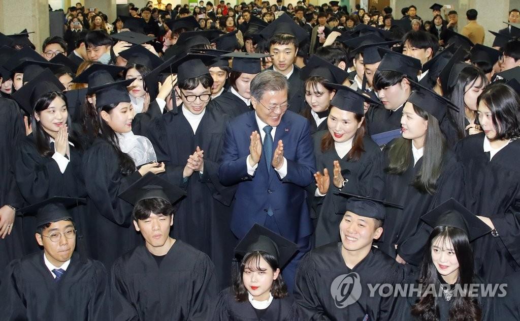 2月21日上午,在京畿道富川市,韩国总统文在寅出席柳韩大学的毕业典礼并与毕业生合影留念。(韩联社)