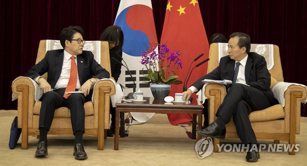 资料图片:2月26日,在北京,韩国环境部部长赵明来(左)同中国生态环境部部长李干杰举行会晤。(韩联社)