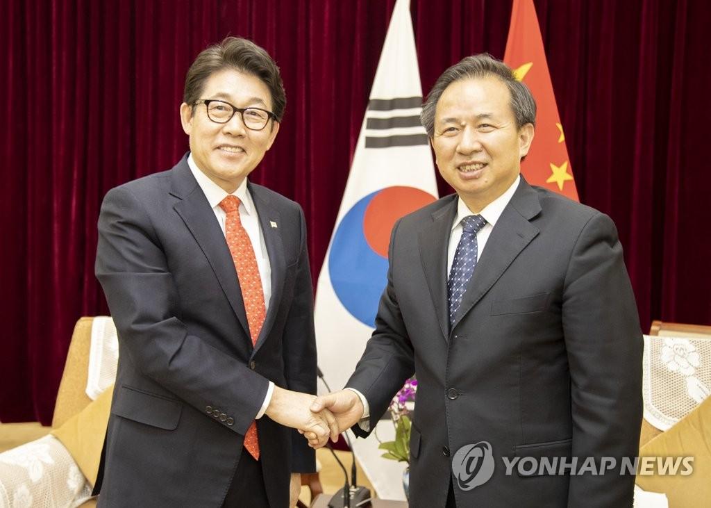 资料图片:2月26日,在北京,韩国环境部长官赵明来(左)同中国生态环境部部长李干杰举行会谈后握手合影。 韩联社/韩国环境部供图