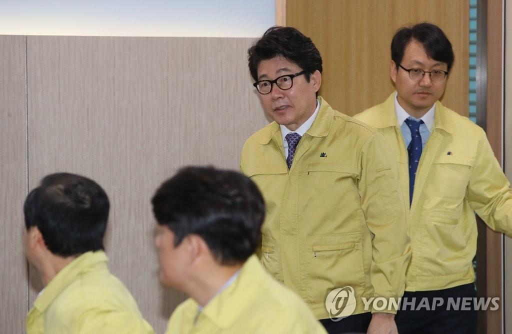 3月5日,在世宗市的韩国环境部,赵明来(右二)身穿民防制服走入重污染天气应急减排措施各市道工作会议现场。(韩联社)
