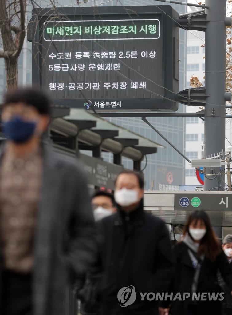 资料图片:3月6日,在首尔市区,市民们戴着口罩上班。(韩联社)
