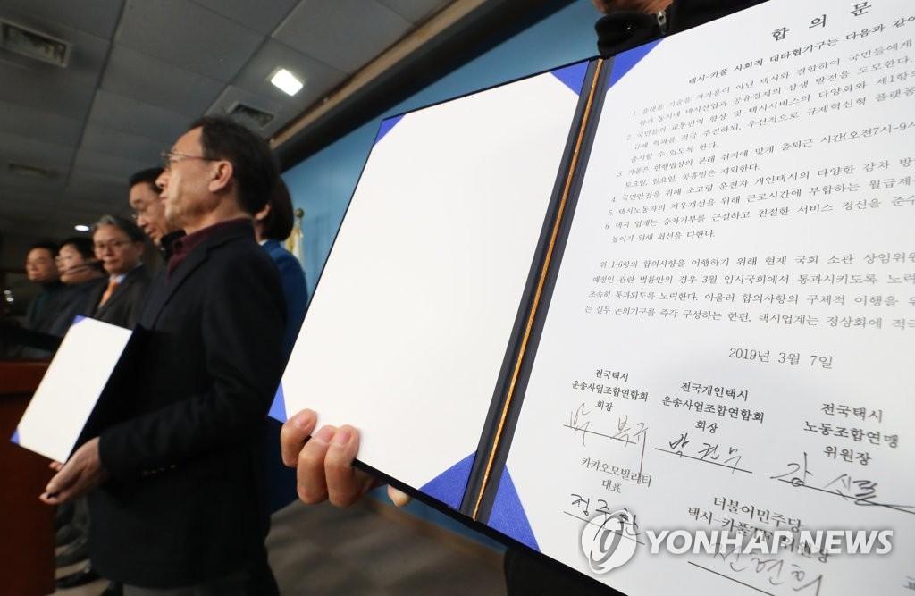 3月7日,在韩国国会,出租车行业四团体代表、拼车软件企业代表与共同民主党专项工作组(TF)委员长全贤姬(中)等有关人士在签署拼车软件相关协议后合影留念。(韩联社)