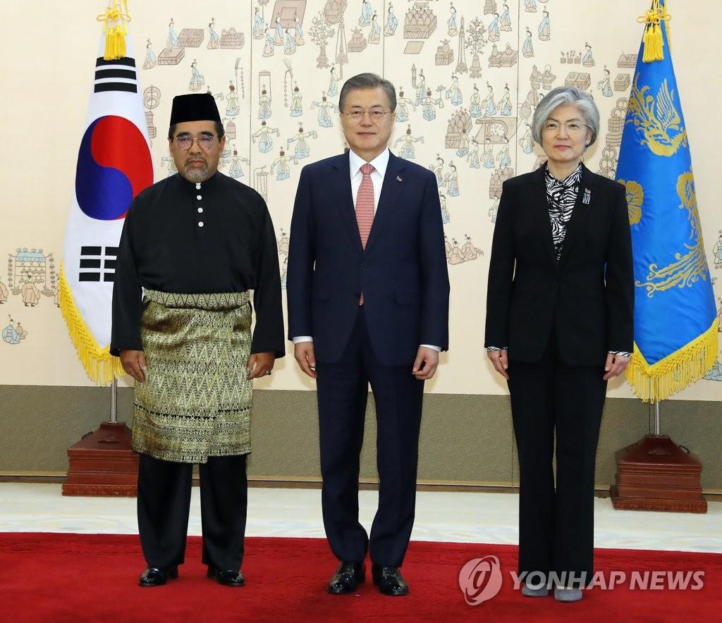 3月8日,在青瓦台,总统文在寅(居中)接受六国新任大使提交的国书后与马来西亚新任大使(左)、韩外长康京和合影留念。(韩联社)