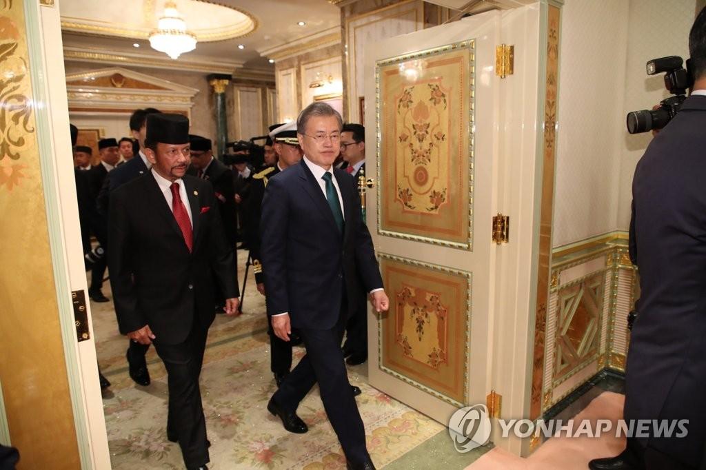 3月11日上午,在文莱王宫,文在寅和博尔基亚走入会场。(韩联社)
