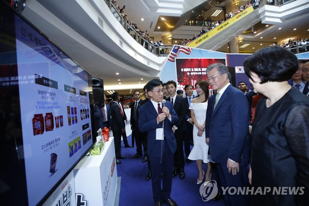 """3月12日下午,在吉隆坡万达购物中心,正在对马来西亚进行国事访问的韩国总统文在寅(右二)携夫人金正淑女士(右一)出席""""韩国-马来西亚韩流与清真展览会""""并听取参展韩企介绍产品。(韩联社)"""