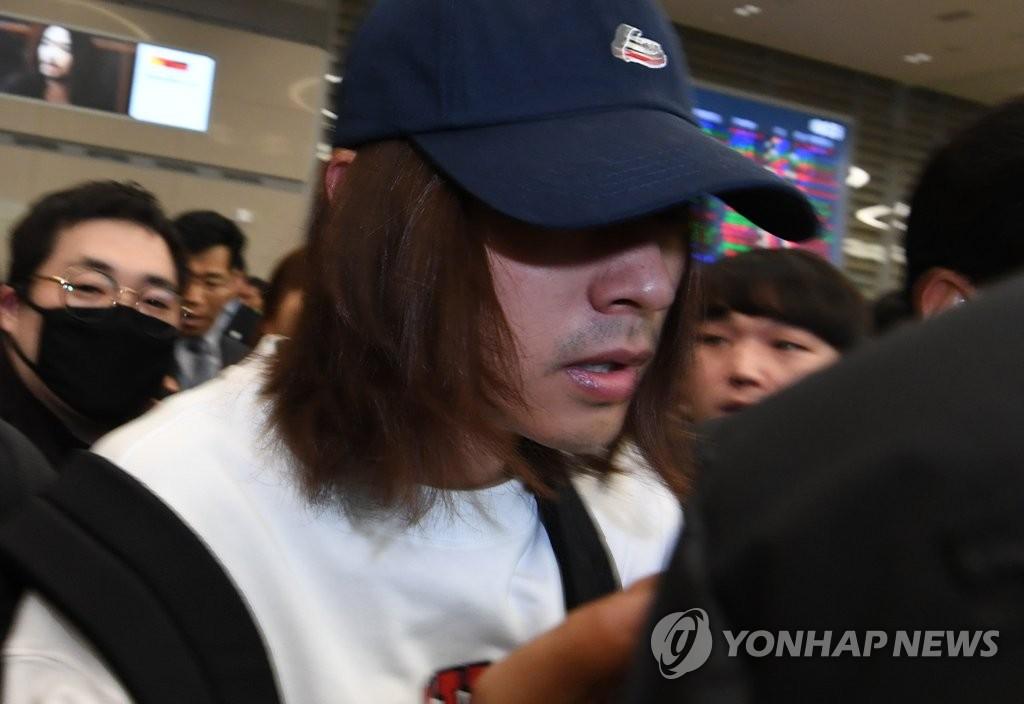 3月12日,在仁川国际机场,涉嫌在聊天群中散布性爱视频的韩国艺人郑俊英返回韩国接受警方调查。(韩联社)