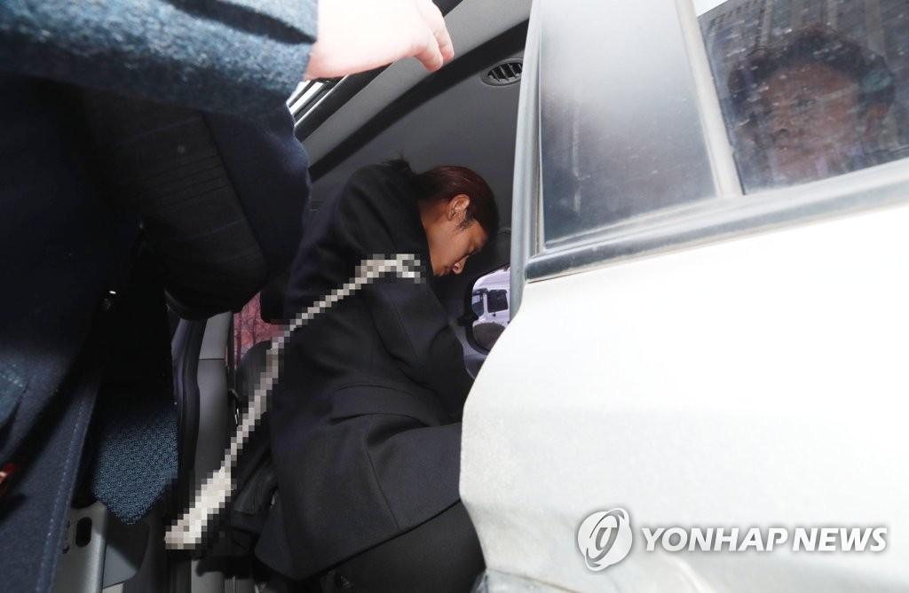 3月21日,在首尔中央地法门口,郑俊英结束逮捕审查后上车离开法院。(韩联社)