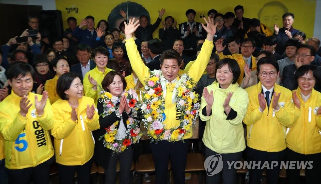 """韩国""""国会议员补选""""投票4月3日正式结束。正义党选人余永国(前排居中)当选庆尚南道昌原市城山选区的国会议员后举手欢呼。(韩联社)"""