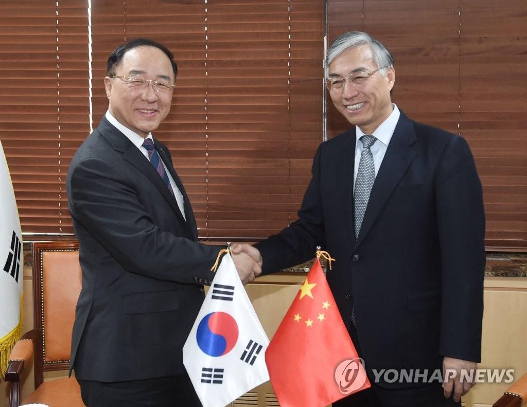 4月19日下午,在首尔,洪楠基(左)和邱国洪握手。(韩联社)