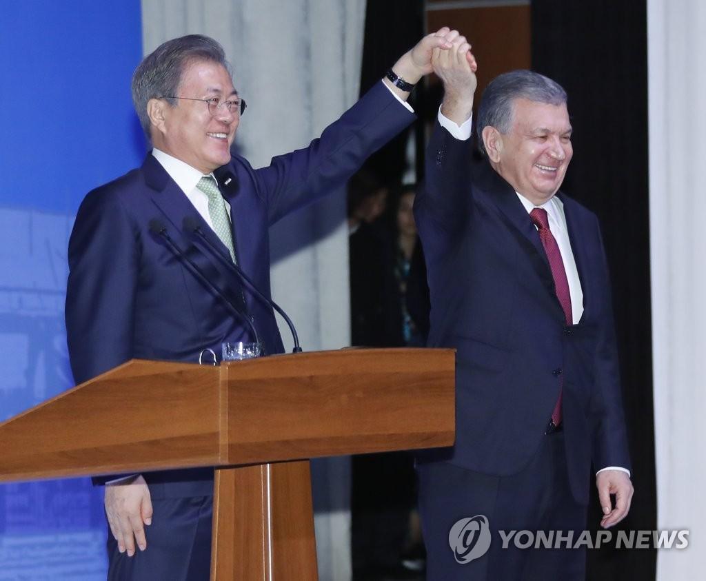 文在寅(左)和米尔济约耶夫(韩联社)