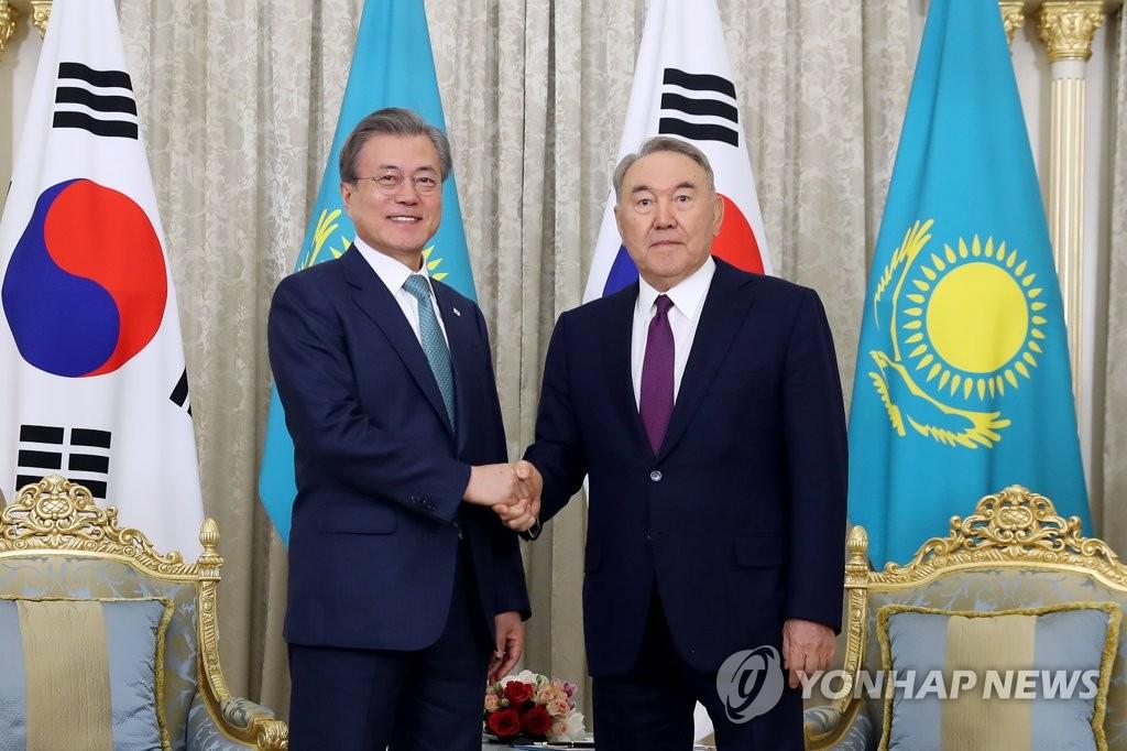 当地时间4月22日下午,正在对哈萨克斯坦进行国事访问的韩国总统文在寅(左)同哈萨克斯坦前总统纳扎尔巴耶夫握手合影。(韩联社)