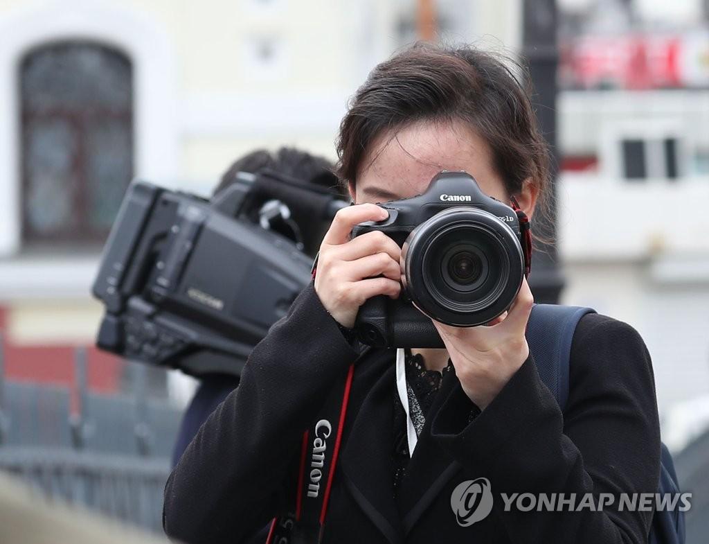 朝鲜记者忙拍照