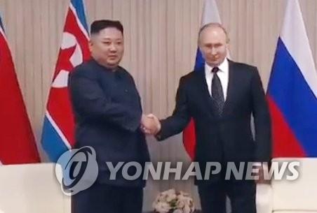 当地时间4月25日,在俄罗斯符拉迪沃斯托克远东联邦大学,朝鲜国务委员会委员长金正恩(左)与俄罗斯总统普京握手合影。韩联社/韩联社TV截图