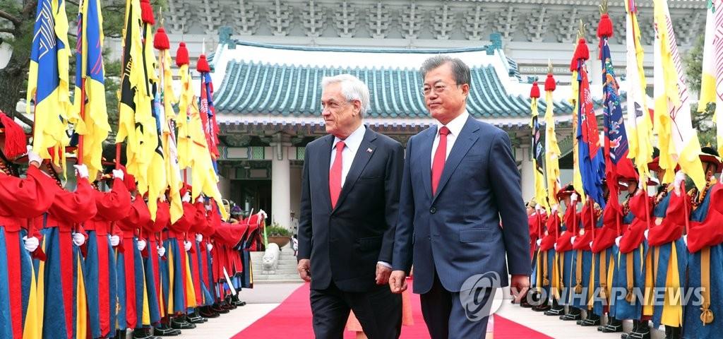 文在寅(右)欢迎皮涅拉。(韩联社)