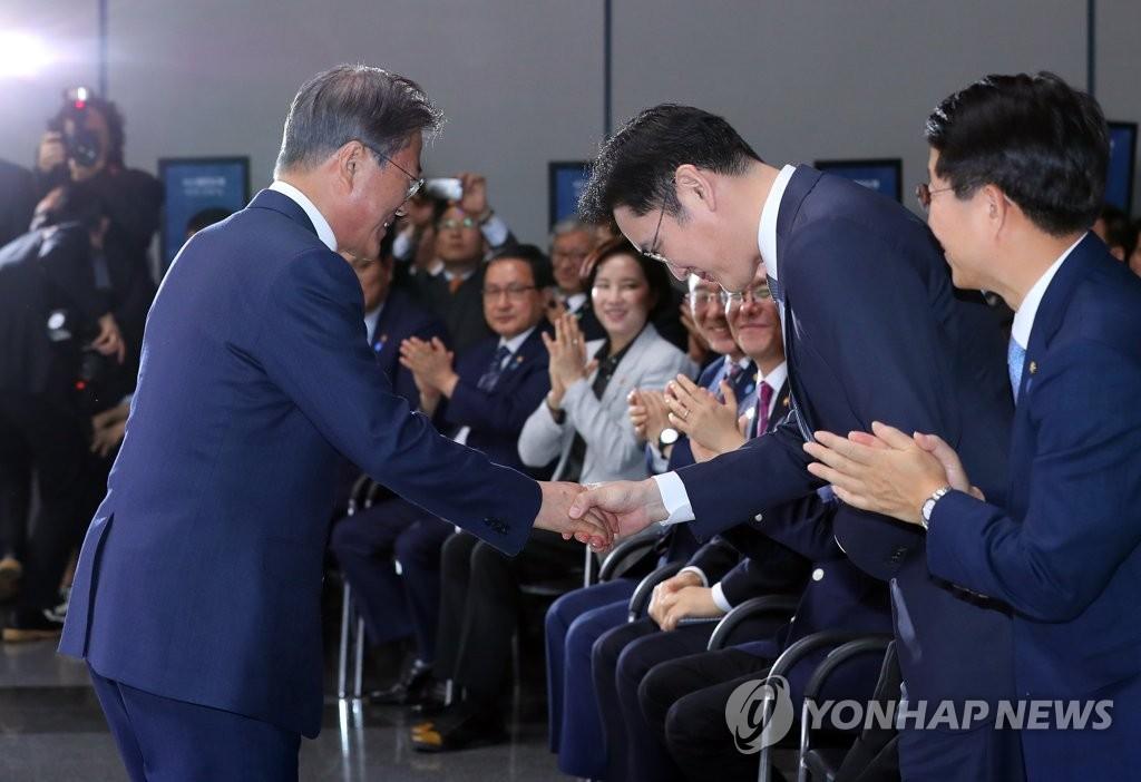 文在寅(左一)同李在镕(右二)亲切握手。(韩联社)