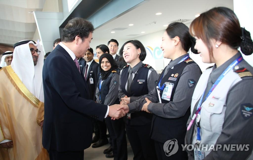 李洛渊(左一)勉励机场工作人员。(韩联社)